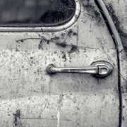 An old car rusted over the years and rotting in a garage.